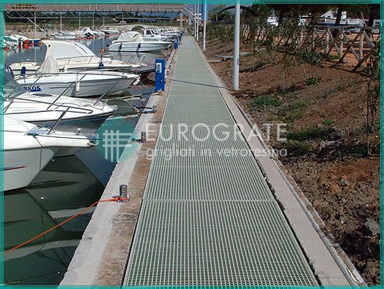passerelle en caillebotis installée dans une zone côtière avec postes d'amarrage pour yachts